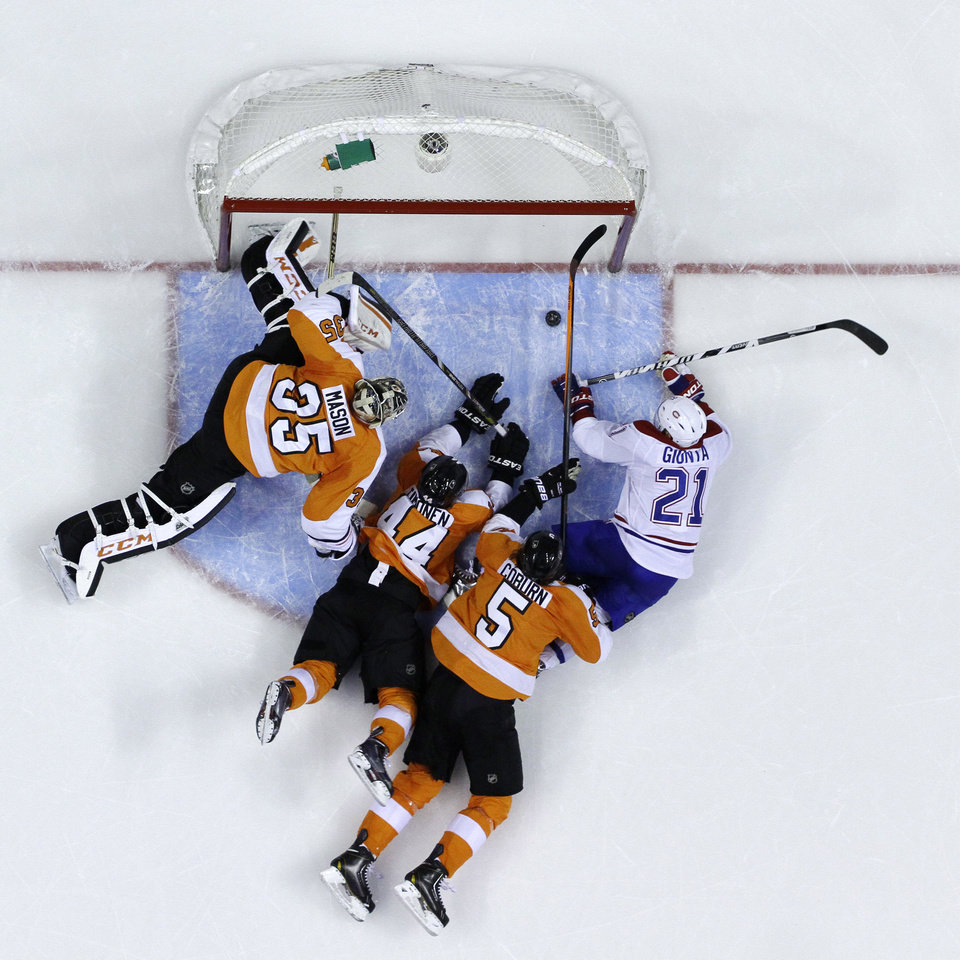 Photo - FILE - In this Dec. 12, 2013, file photo, Montreal Canadiens' Brian Gionta (21) knocks in a goal with his hand against Philadelphia Flyers' Braydon Coburn (5), Kimmo Timonen (44), of Finland, and Steve Mason (35) during the third period of an NHL hockey game in Philadelphia. The goal was overturned. For the first time since 1973, there is just one Canadian team in the NHL postseason. The Canadiens represent the nation's only hope of ending a 21-year Stanley Cup drought. (AP Photo/Matt Slocum, File)