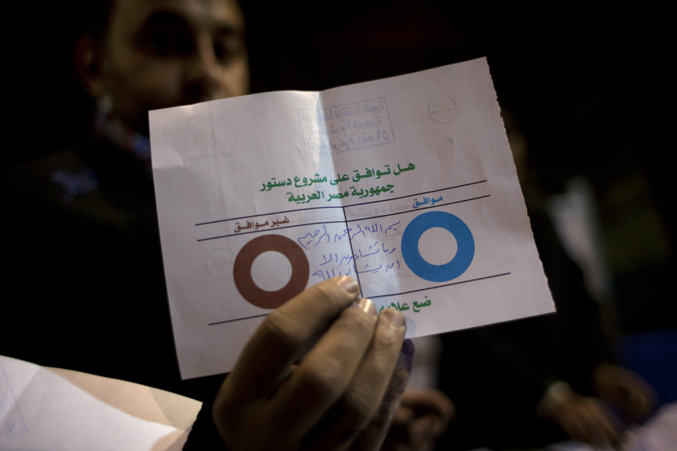 Photo - An Egyptian election worker shows his colleagues an invalid ballot while counting ballots at the end of the second round of a referendum on a disputed constitution drafted by Islamist supporters of president Mohammed Morsi at a polling station in Giza, Egypt, Saturday, Dec. 22, 2012. Egypt's Islamist-backed constitution headed toward likely approval in a final round of voting on Saturday, but the deep divisions it has opened up threaten to fuel continued turmoil. (AP Photo/Nasser Nasser)