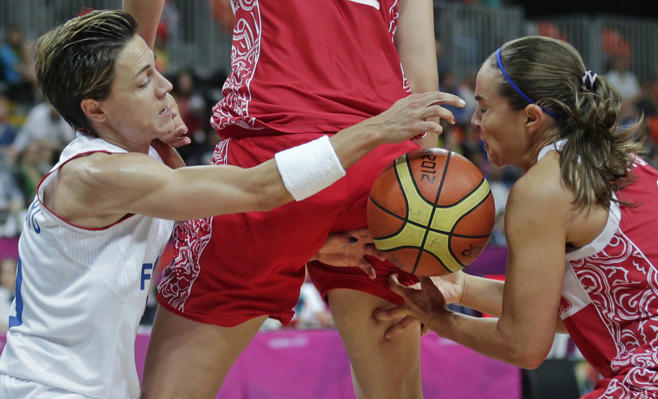 Photo - France's Celine Dumerc, left, reaches through the legs of Russia's Natalya Vieru while battling for a loose ball with Becky Hammon during a women's basketball game at the 2012 Summer Olympics, Sunday, Aug. 5, 2012, in London. (AP Photo/Charles Krupa)