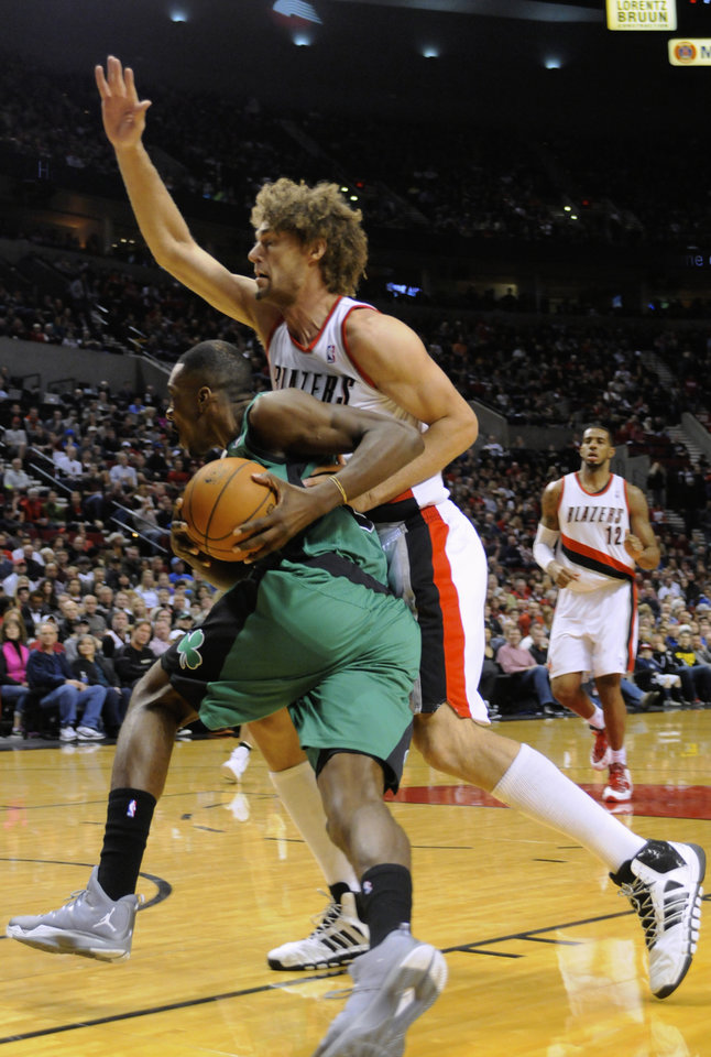Photo - Boston Celtics' Jeff Green, bottom, drives against Portland Trail Blazers' Robin Lopez during the first half of an NBA basketball game in Portland, Ore., Saturday, Jan. 11, 2014. (AP Photo/Greg Wahl-Stephens)