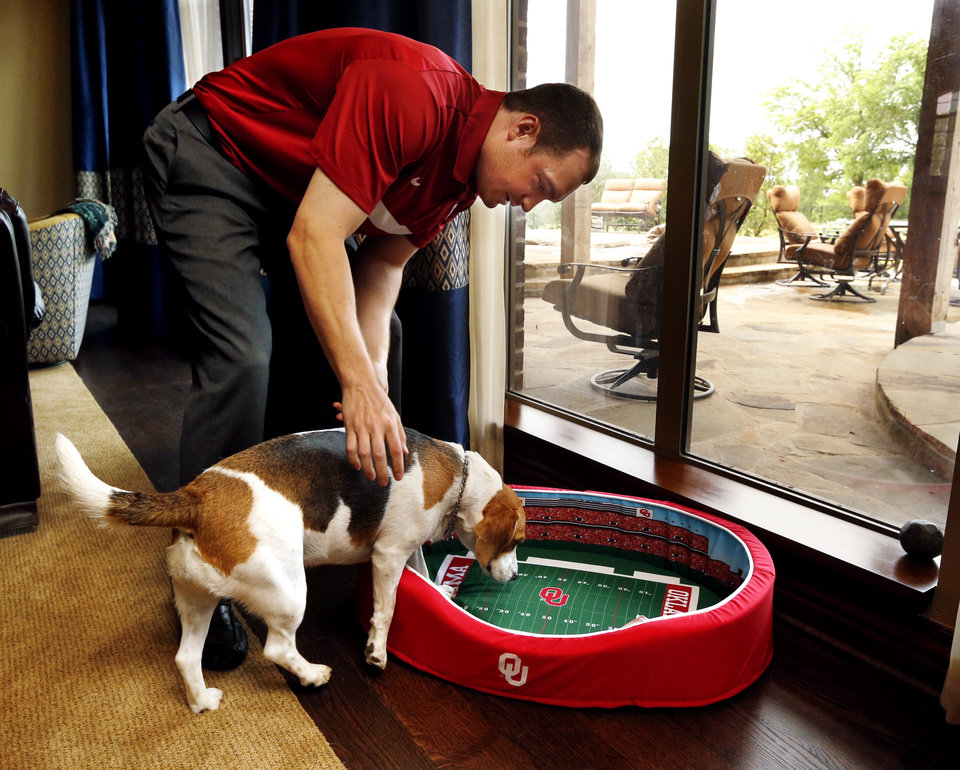 Photo -  Kevin Kruger and his pet, Miss Dixie Mae, show pet beds Thursday in Norman that he designed and sells that look like college football stadiums. Photo by Steve Sisney, The Oklahoman   STEVE SISNEY -