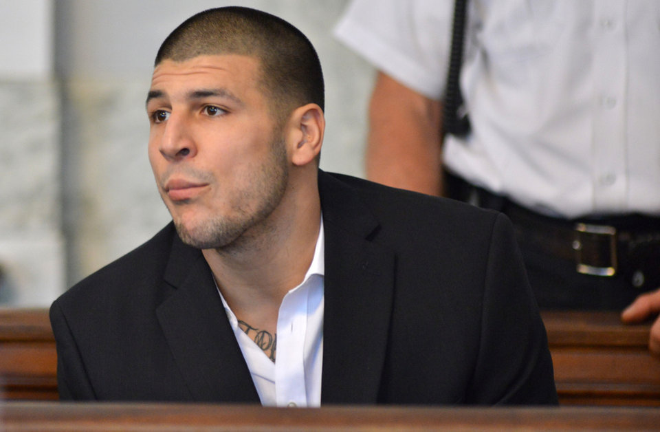 Photo - Former New England Patriot football player Aaron Hernandez, listens to procedings in a court in Attleboro, Mass., Thursday, Aug. 22, 2013. Hernandez was indicted on first-degree murder and weapons charges in the death of a friend whose bullet-riddled body was found in an industrial park about a mile from the ex-player's home. (AP Photo/Josh Reynolds)