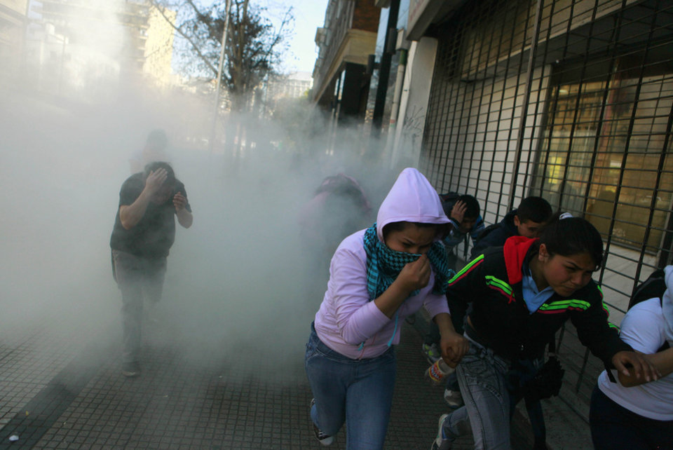 Photo -   People run from teargas fired by police during a protest demanding free education in Santiago, Chile, Wednesday, Aug. 8, 2012. Police used water cannons and tear gas to break up the protest and three buses were set ablaze. (AP Photo/Luis Hidalgo)