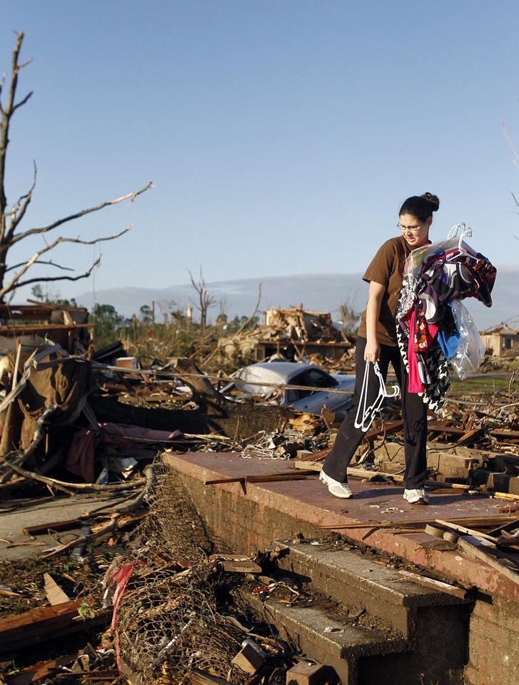 Photo - Tiffany Wood carries clothes from her home Thursday, April 28, 2011 after a tornado hit Pleasant Grove just west of downtown Birmingham, Ala., Wednesday afternoon. (AP Photo/Butch Dill)
