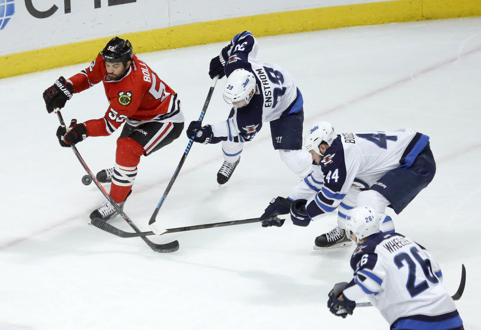 Photo - Chicago Blackhawks left wing Brandon Bollig (52) is unable to get a shot-on-goal from the defense of Winnipeg Jets defenseman Tobias Enstrom (39) Zach Bogosian (44) and Blake Wheeler during the first period of an NHL hockey game, Sunday, Jan. 26, 2014, in Chicago. (AP Photo/Charlie Arbogast)