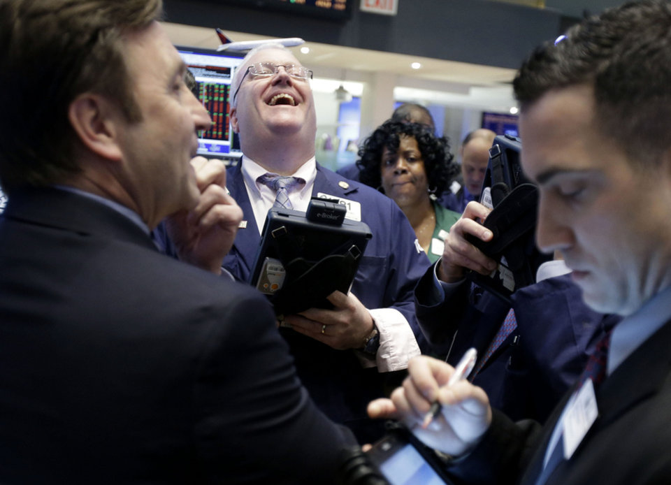 A trader laughs Thursday while working on the floor of the New York Stock Exchange.  AP Photo
