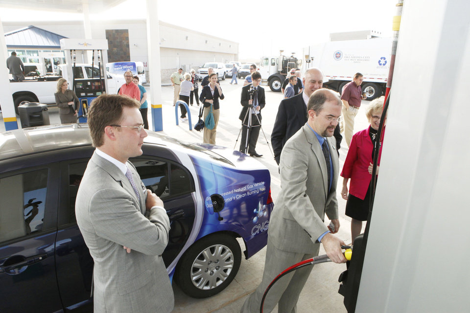 Oklahoma Energy Secretary Bobby Wegener looks on as Environment Secretary J. D. Strong fills up his car with compressed natural gas at the new Total Express store Monday in northwest Oklahoma City. Photo by Paul Hellstern, The Oklahoman