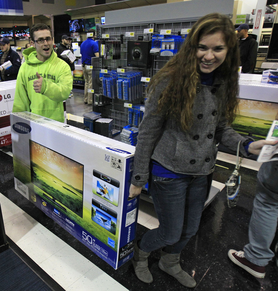 Josh Blankfeld, left to right, gives a thumbs-up as Blankfeld and Erin Burke carry a 50-inch television to the checkout at a Best Buy Friday, Nov. 23, 2012, in Mayfield Heights, Ohio. The store opened at 12 a.m. on Friday. (AP Photo/Tony Dejak)