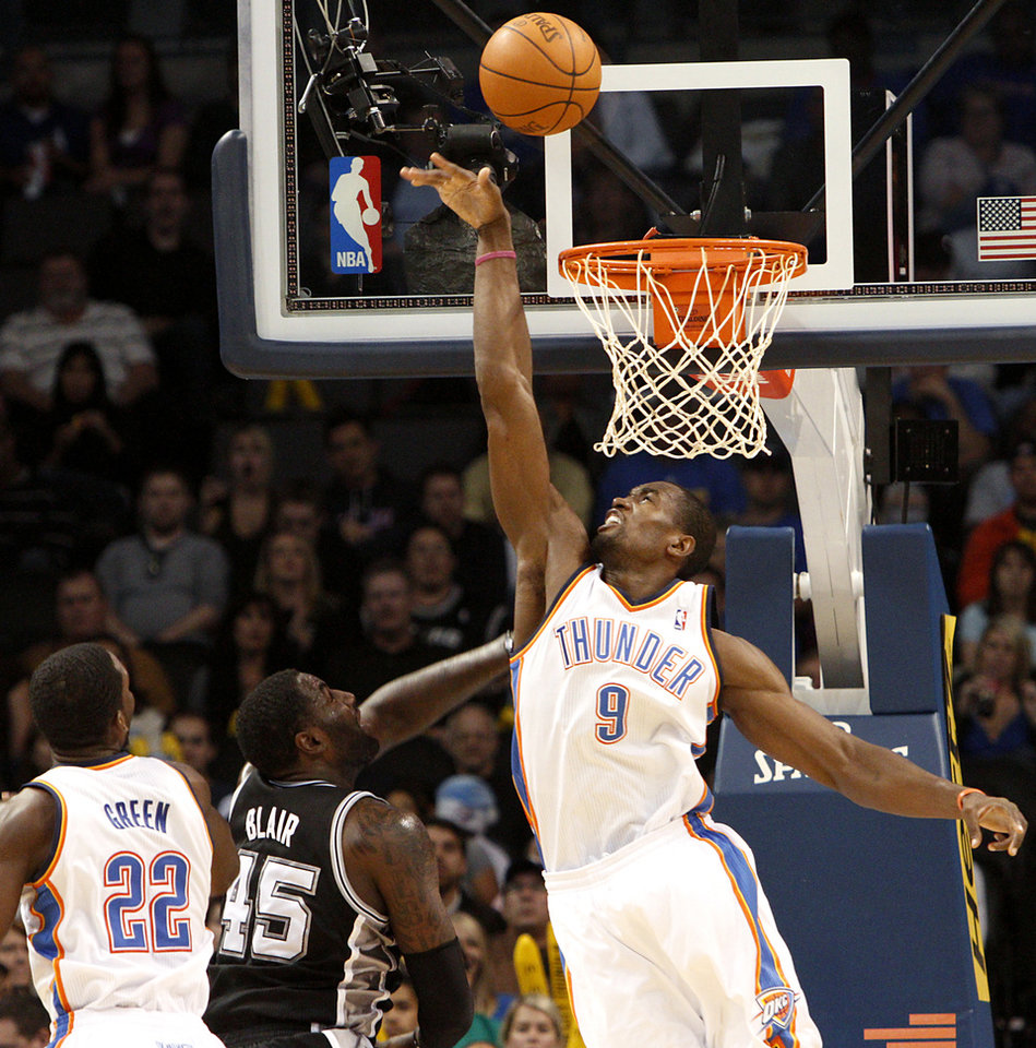 Photo - Oklahoma City's Serge Ibaka tries to block a shot by  San Antonio's DeJuan Blair during their NBA basketball game in downtown Oklahoma City  on Sunday, Nov. 14, 2010. The Thunder lost to the Spurs 117-104.  Photo by John Clanton, The Oklahoman