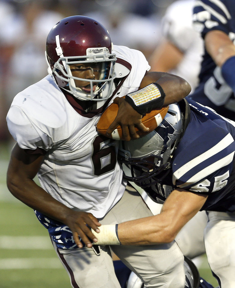 Photo - Edmond Memorial's Warren Wand is tackled by Edmond North's Joel Dixon during the high school football game between Edmond North and Edmond Memorial at Wantland Stadium in Edmond, Okla., Friday, Aug. 31, 2012. Photo by Sarah Phipps, The Oklahoman