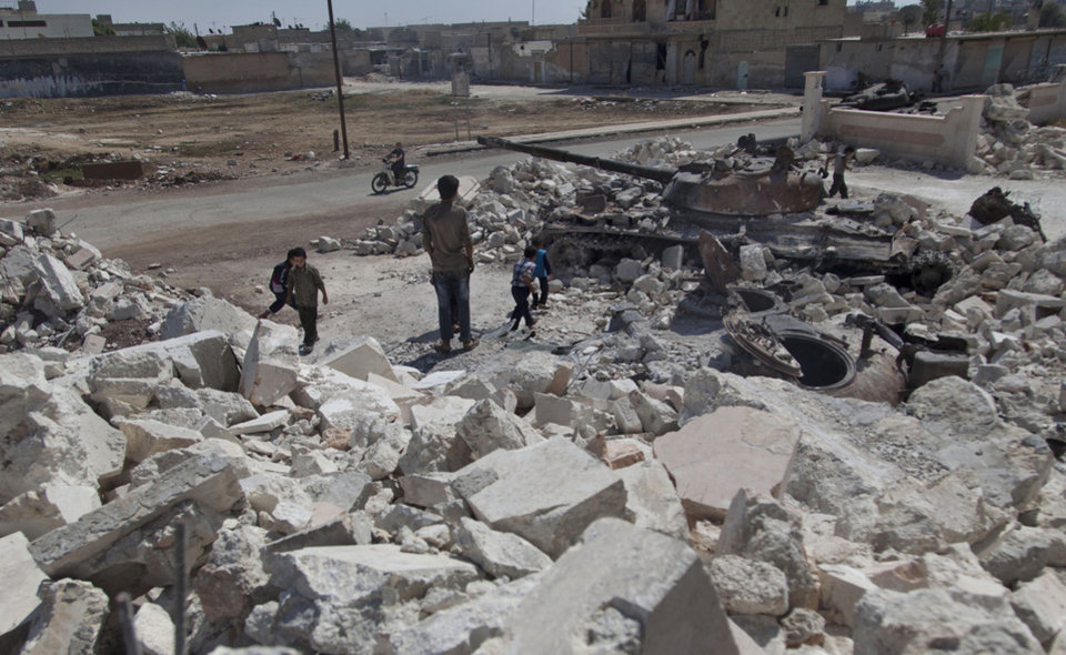 Photo -   In this Wednesday, Aug. 15, 2012 photo, Syrian children play near a destroyed military tank next to the rubble of a damaged building in town of Azaz on the outskirts of Aleppo, Syria. Thousands of Syrians who have been displaced by the country's civil are struggling to find safe shelter while shelling and airstrikes by government forces continue. (AP Photo/ Khalil Hamra)