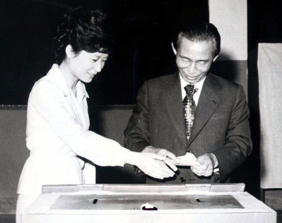 Photo - FILE - In this 1977 file photo, then South Korean President Park Chung-hee, right, and his daughter, Park Geun-hye, cast ballots in Seoul, South Korea. Park Geun-hye was elected the country's first female president Wednesday, Dec. 19, 2012, a landmark win that could mean a new drive to start talks with rival North Korea. (AP Photo/Yonhap, File) KOREA OUT