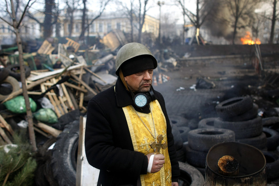 Photo - A priest stands on the barricades at Independence Square in Kiev, Ukraine, Friday, Feb. 21, 2014. Ukraine's presidency said Friday that it has negotiated a deal intended to end battles between police and protesters that have killed scores and injured hundreds, but European mediators involved in the talks wouldn't confirm a breakthrough. (AP Photo/ Marko Drobnjakovic)