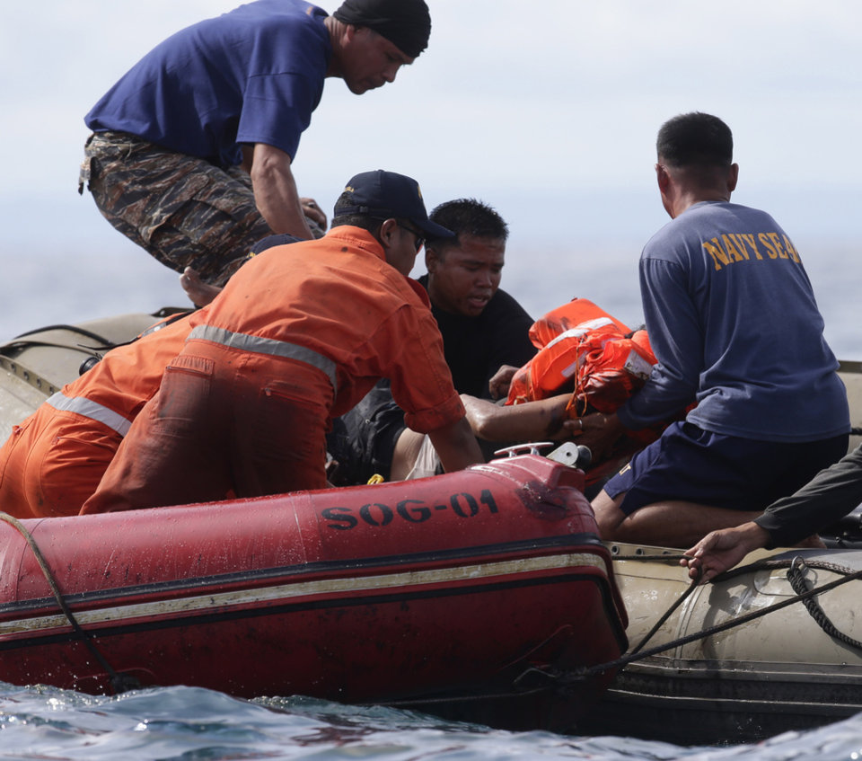 Photo - Philippine Navy and Philippine Coast Guard divers retrieve a body from the waters off the coast of Talisay city, Cebu province, in central Philippines Saturday Aug. 17, 2013, a day after a passenger ferry MV Thomas of Aquinas collided with a cargo ship Sulpicio Express Siete. Divers combed through a sunken ferry Saturday to retrieve the bodies of more than 200 people still missing from an overnight collision with a cargo vessel near the central Philippine port of Cebu that sent passengers jumping into the ocean and leaving many others trapped. At least 28 were confirmed dead and hundreds rescued. The captain of the ferry MV Thomas Aquinas, which was approaching the port late Friday, ordered the ship abandoned when it began listing and then sank just minutes after collision with the MV Sulpicio Express, coast guard deputy chief Rear Adm. Luis Tuason said. (AP Photo/Bullit Marquez)