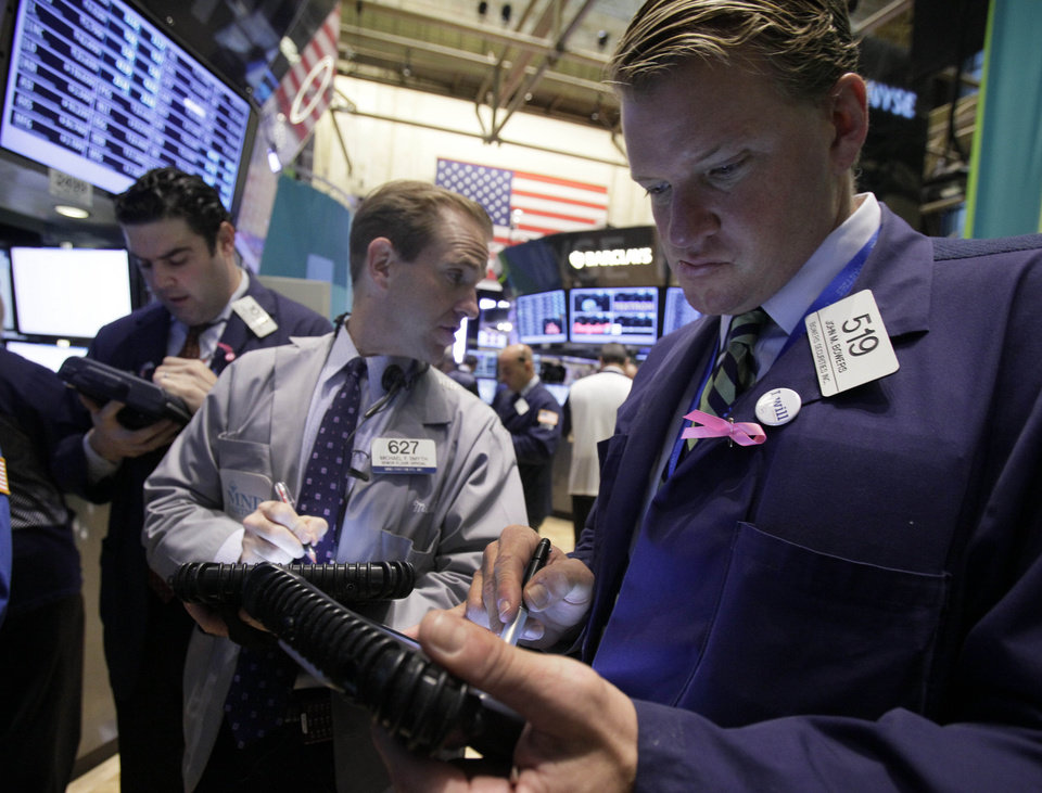 Photo -   John Bowers, right, works with fellow traders on the floor of the New York Stock Exchange Thursday, Oct. 18, 2012. The U.S. stock market headed slightly lower on Thursday, following a leap in claims for unemployment benefits and weak results from American Express. (AP Photo/Richard Drew)