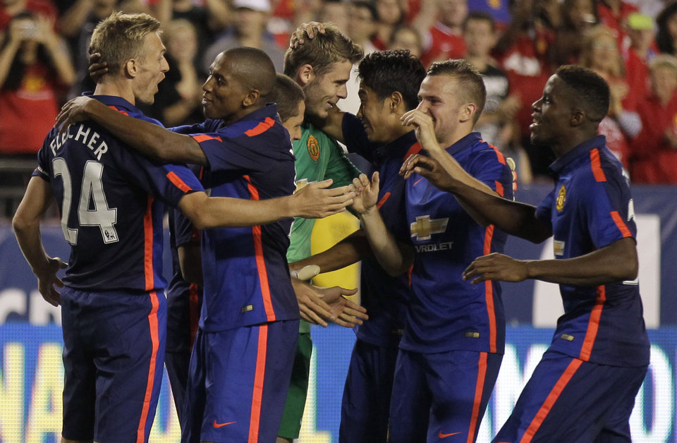 Photo - Manchester United's Darren Fletcher (24) celebrates with his teammates after  scoring the winning kick in a penalty kick shootout during  a soccer game at the 2014 Guinness International Champions Cup, Tuesday, July 29, 2014, in Landover, Md. Manchester United won 5-3 in penalty kicks. (AP Photo/Luis M. Alvarez)