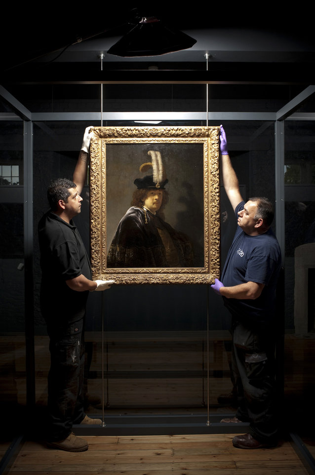 Photo - This undated handout photo provided by the National Trust shows Simon Jacobs, left, and Martyn Bartle carefully hanging the self-portrait of Rembrandt which has returned to Buckland Abbey, Devon, England.  Scientific tests have confirmed that a painting donated to Britain's National Trust by a wealthy supporter is a Rembrandt self-portrait worth tens of millions of pounds (dollars). The painting was given to the heritage body in 2010 and hangs in Buckland Abbey in southwest England, former home of 16th-century seafarer Francis Drake. (AP Photo/ Steven Haywood/National Trust, PA) UNITED KINGDOM OUT
