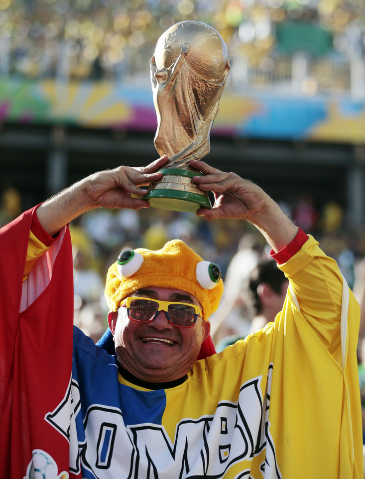 Photo - A spectator holds up a replica of the World Cup trophy before the group A World Cup soccer match between Brazil and Croatia, the opening game of the tournament, in the Itaquerao Stadium in Sao Paulo, Brazil, Thursday, June 12, 2014.  (AP Photo/Ivan Sekretarev)