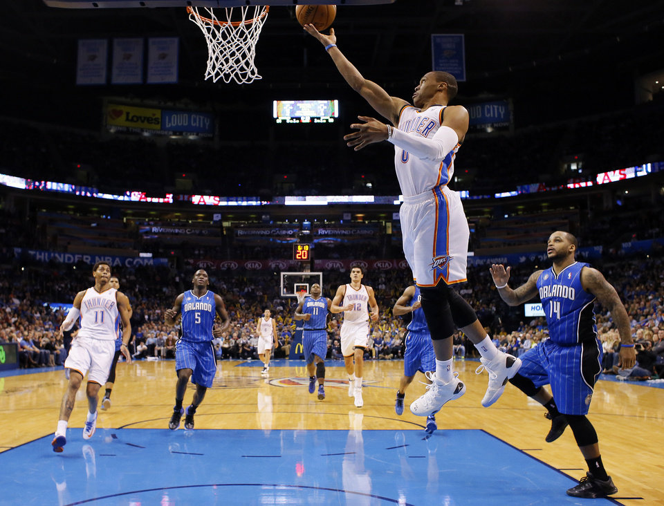 Oklahoma City�s Russell Westbrook, center, shoots a layup in front of Orlando�s Jameer Nelson during Sunday�s game. Photo by Sarah Phipps, The Oklahoman
