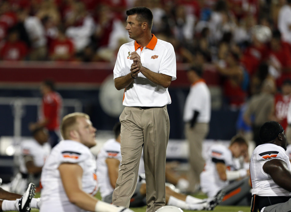 Photo - Oklahoma State head coach Mike Gundy watches warm ups before the college football game between the University  of Arizona and Oklahoma State University at Arizona Stadium in Tucson, Ariz.,  Saturday, Sept. 8, 2012. Photo by Sarah Phipps, The Oklahoman