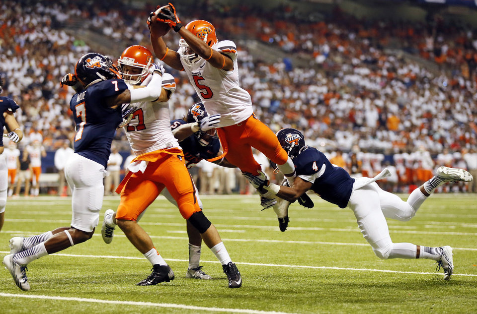 OSU's Josh Stewart (5) leaps for the end zone while defended by UTSA's Blake Terry (52) and Crosby Adams II (4) as OSU's Charlie Moore (17) blocks UTSA's Triston Wade (7) in the second quarter during a college football game between the University of Texas at San Antonio Roadrunners (UTSA) and the Oklahoma State University Cowboys (OSU) at the Alamodome in San Antonio, Saturday, Sept. 7, 2013. Stewart reached the end zone on a second effort after the leap. Photo by Nate Billings, The Oklahoman