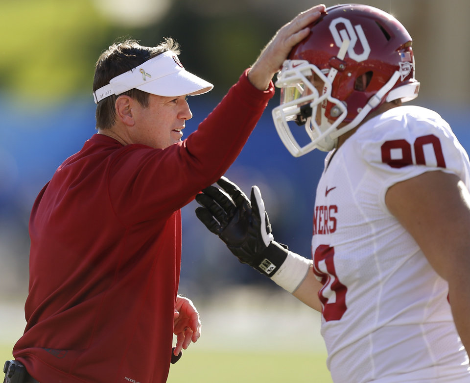 Oklahoma coach Bob Stoops taps the helmet of OU\'s Matt Dimon (90) after a punt block during the college football game between the University of Oklahoma Sooners (OU) and the University of Kansas Jayhawks (KU) at Memorial Stadium in Lawrence, Kan., Saturday, Oct. 19, 2013. Oklahoma won 34-19. Photo by Bryan Terry, The Oklahoman