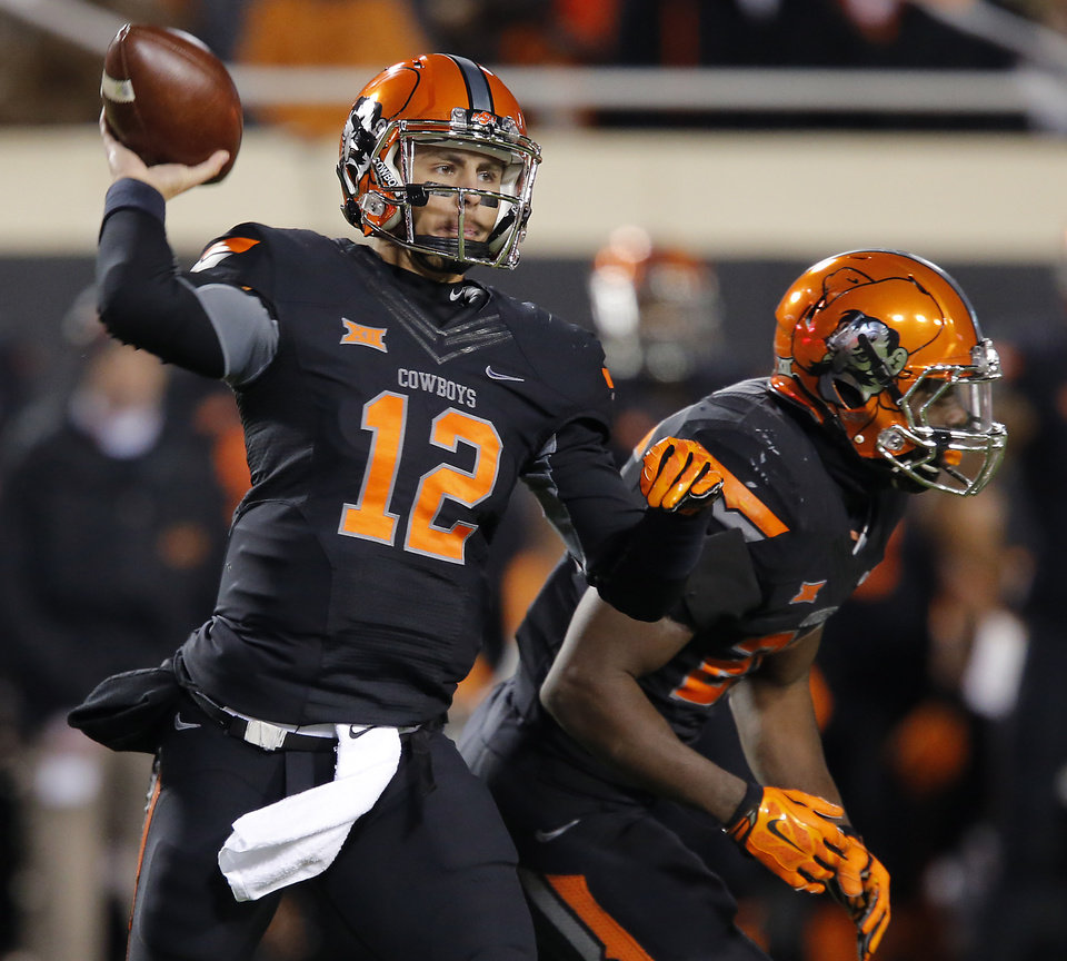 Photo - Oklahoma State's Daxx Garman (12) looks to throw the ball during the college football game between the Oklahoma State University Cowboys (OSU) the University of Texas Longhorns (UT) at Boone Pickens Staduim in Stillwater, Okla. on Saturday, Nov. 15, 2014.  Photo by Chris Landsberger, The Oklahoman