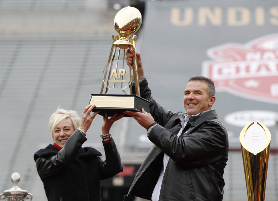 Photo - Ohio State coach Urban Meyer, right, and The Associated Press' east regional director Eva Parziale hold up The Associated Press college football national championship trophy during a celebration of the Buckeye's 2014 College Football Playoff national champion  at Ohio Stadium in Columbus, Ohio, Saturday, Jan. 24, 2015. (AP Photo/Paul Vernon)