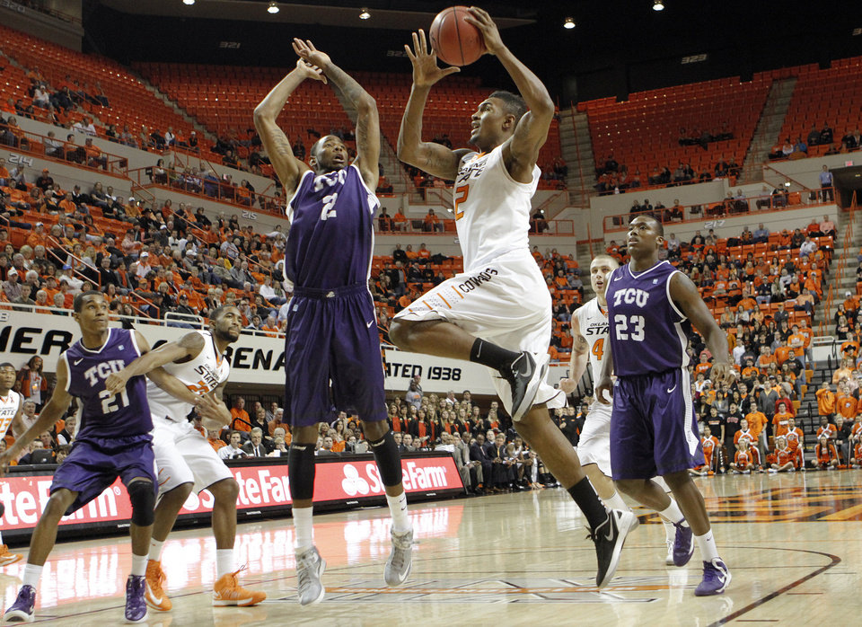 Photo - Oklahoma State's Le'Bryan Nash (2) drives past TCU's Connell Crossland (2) and Devonta Abron (23) during the college basketball game between Oklahoma State University Cowboys (OSU) and Texas Christian University Horned Frogs (TCU) at Gallagher-Iba Arena on Wednesday Jan. 9, 2013, in Stillwater, Okla. 