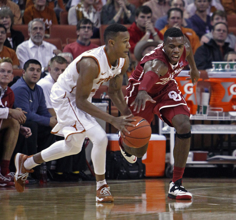 Photo - Oklahoma guard Buddy Hield , right, fights for the loose ball with Texas guard Demarcus Holland, left, during the second half an NCAA college basketball game, Monday, Jan. 5, 2015, in Austin, Texas. Oklahoma won 70-49.  (AP Photo/Michael Thomas)