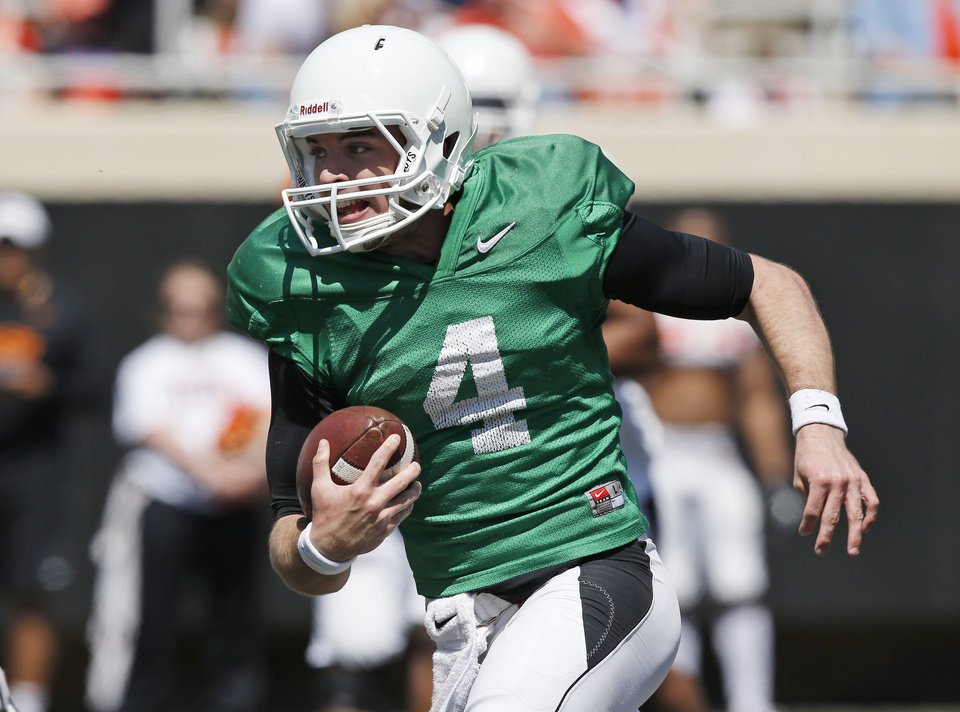 Photo - Oklahoma State quarterback J.W. Walsh (4) carries the ball during an Orange Blitz NCAA college spring football practice in Stillwater, Okla., Saturday, April 5, 2014. (AP Photo/Sue Ogrocki)