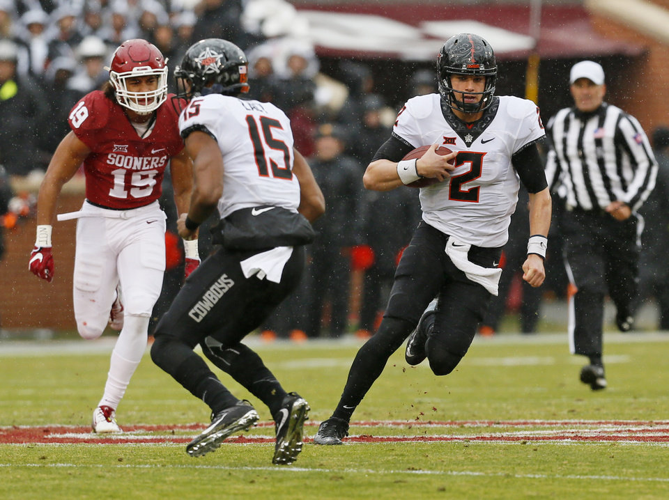 Photo - Oklahoma State's Mason Rudolph (2) carries the ball near Chris Lacy (15) and Oklahoma's Caleb Kelly (19) during the Bedlam college football game between the Oklahoma Sooners (OU) and the Oklahoma State Cowboys (OSU) at Gaylord Family - Oklahoma Memorial Stadium in Norman, Okla., Saturday, Dec. 3, 2016. Photo by Nate Billings, The Oklahoman