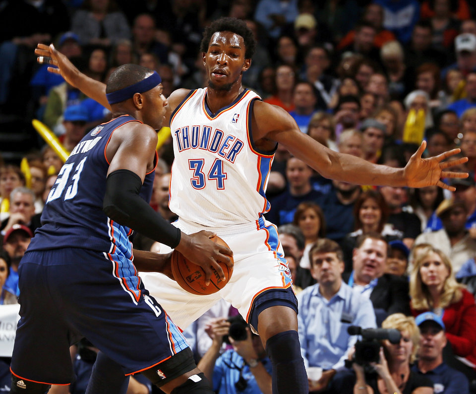 Photo - Oklahoma City's Hasheem Thabeet (34) defends Charlotte's Brendan Haywood (33) during an NBA basketball game between the Oklahoma City Thunder and Charlotte Bobcats at Chesapeake Energy Arena in Oklahoma City, Monday, Nov. 26, 2012.  Photo by Nate Billings , The Oklahoman