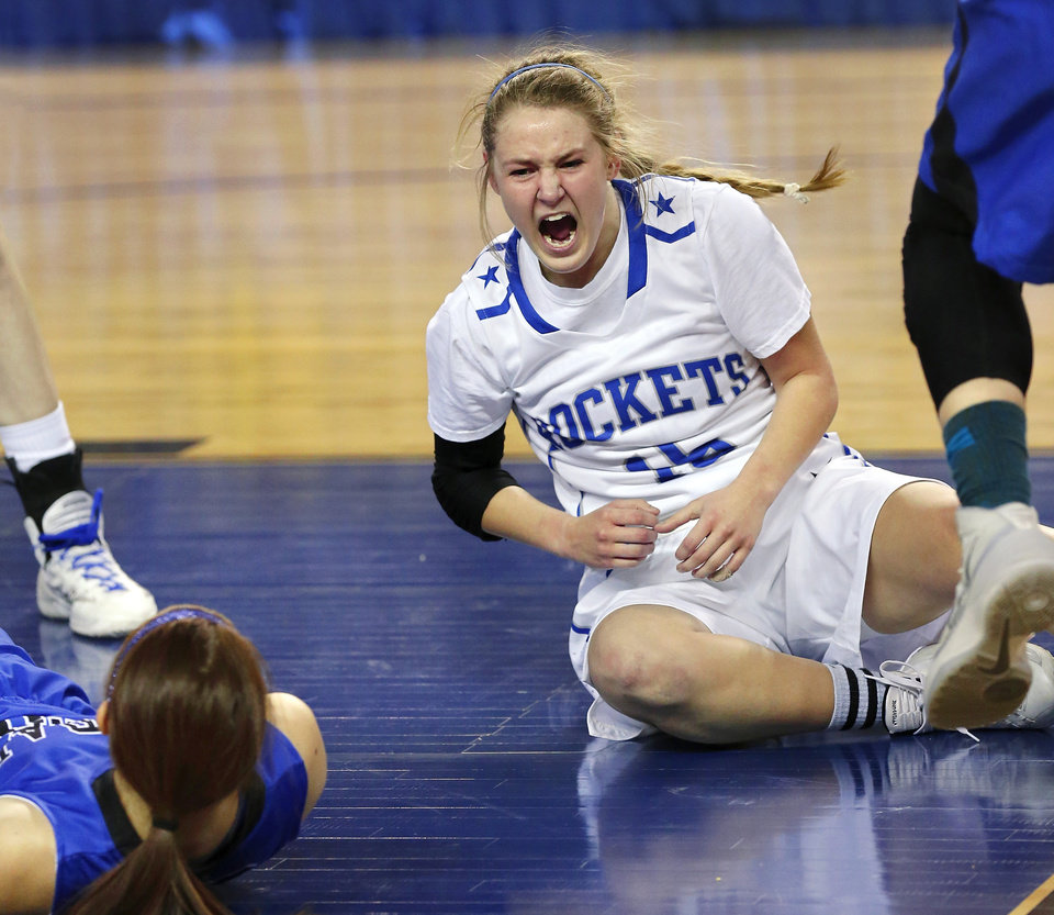 Photo - St. Mary  guard Jordan Hagood grimaces and screams out after taking a hard fall to the floor when she tried to squeeze between Harrah players Maddison Collyer and Grace Brzozowski for a lay-up attempt in the first half of the Class 4A girls basketball quarterfinal game between Mount St. Mary and Harrah at Jim Norick Arena at State Fair Park  on Thursday night, Mar. 13, 2014. Photo by Jim Beckel, The Oklahoman