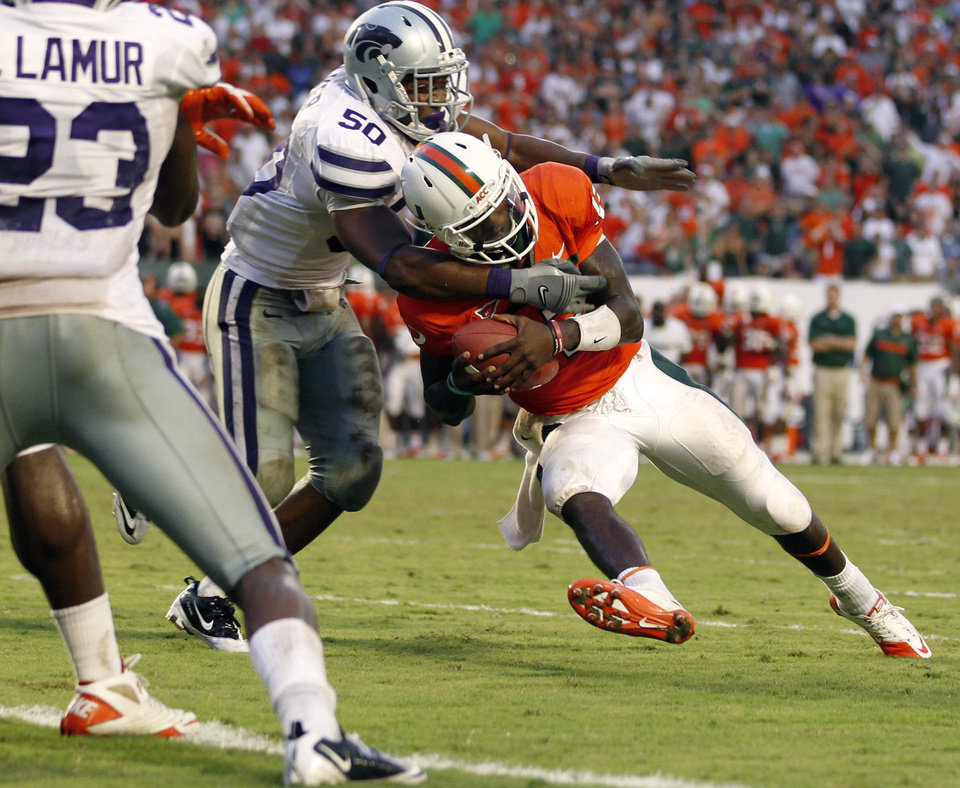 Photo - Miami quarterback Jacory Harris, right, is stopped at the goal line by Kansas State's Tre Walker in the final minute of an NCAA college football game against Kansas State, Saturday, Sept. 24, 2011, in Miami. Kansas State defeated Miami 28-24. (AP Photo/The Miami Herald, Al Diaz) MAGS OUT ORG XMIT: FLMIH112