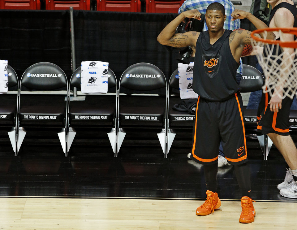 Photo - OSU's Marcus Smart flexes his arms during practice the day before Oklahoma State's second round game of the NCAA men's college basketball tournament at Viejas Arena in San Diago, Thursday, March 20, 2014. Oklahoma State will face Gonzaga in their NCAA Tournament game on Friday, March 21, 2104. Photo by Bryan Terry, The Oklahoman