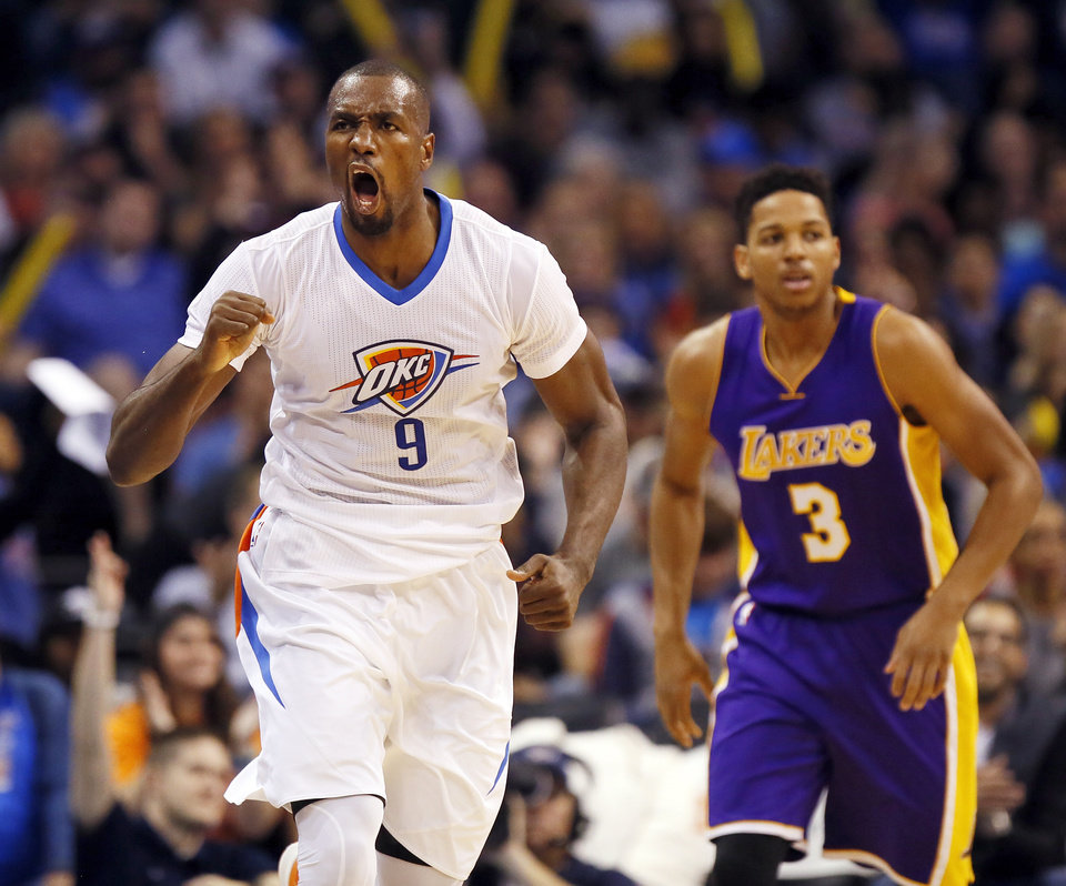 Photo - Oklahoma City's Serge Ibaka (9) reacts in front of Los Angeles' Anthony Brown (3) after making a three-point shot during an NBA basketball game between the Oklahoma City Thunder and the Los Angeles Lakers at Chesapeake Energy Arena in Oklahoma City, Saturday, Dec. 19, 2015. Oklahoma City won 118-78. Photo by Nate Billings, The Oklahoman