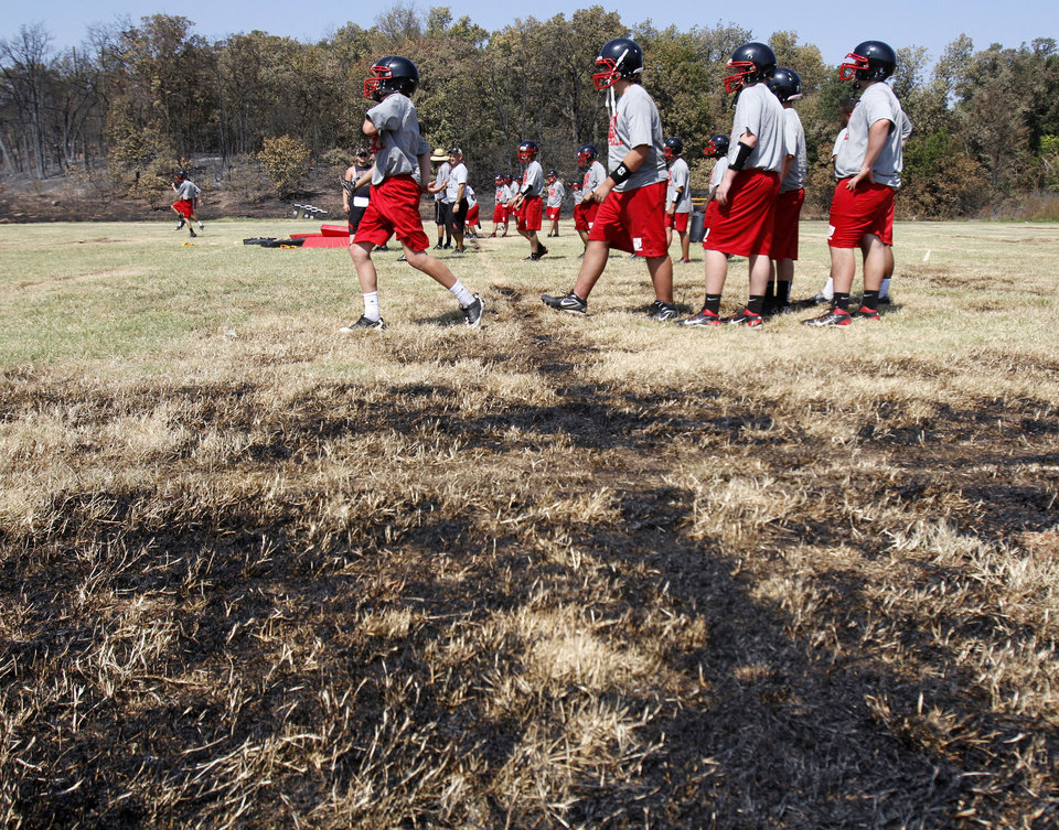 WILDFIRE / AFTERMATH / DAMAGE: Luther High School football players work out on the practice field which was partially burned by recent wildfires in Luther, OK, Tuesday, August 7, 2012, By Paul Hellstern, The Oklahoman