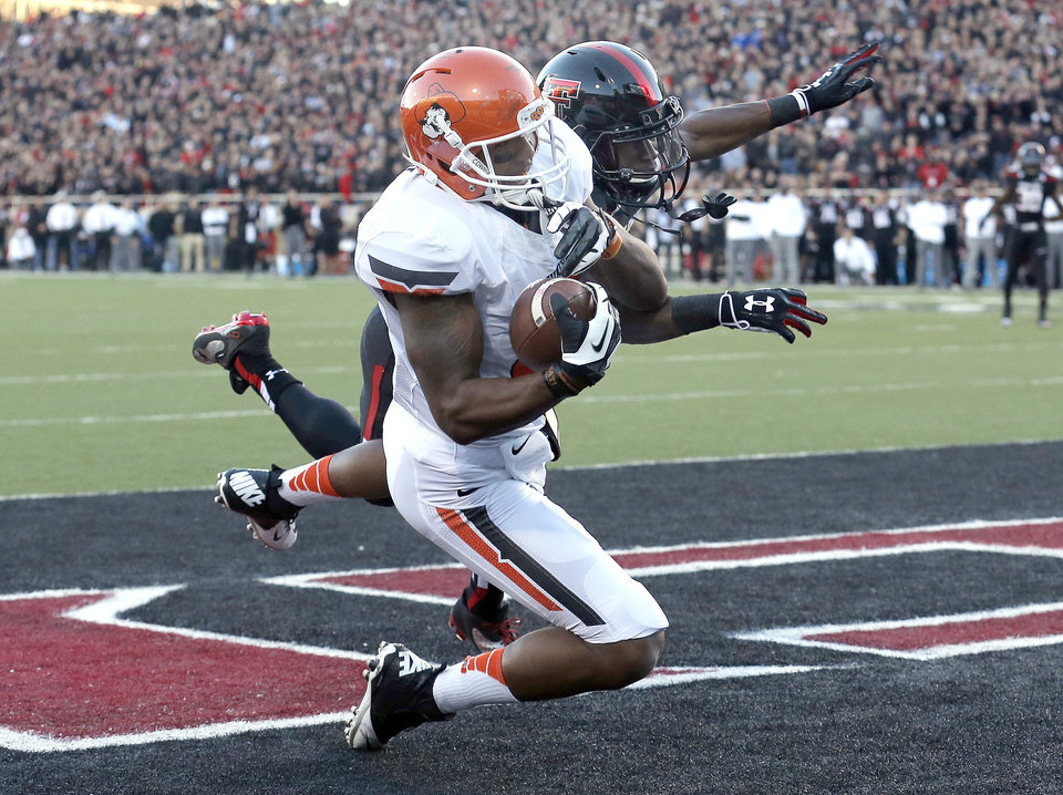 Oklahoma State 's Tracy Moore (87) scores a touchdown as Texas Tech's Derrick Mays (4) defends during the college football game between the Oklahoma State Cowboys (OSU) and the Texas Tech Red Raiders (TTU) at Jones AT&T Stadium in Lubbock, Texas, Saturday, Nov. 2, 2013. Photo by Sarah Phipps, The Oklahoman