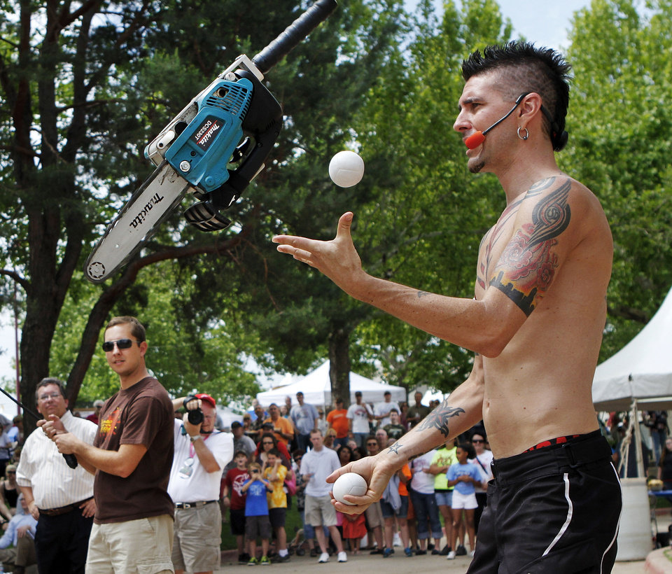 Photo - Comedian, contortionist and daredevil Al Millar, 34, juggles a small chainsaw during his high-energy performs his high-energy show Thursday during the Festival of the Arts. As the event's official street performer, the native Australian known as