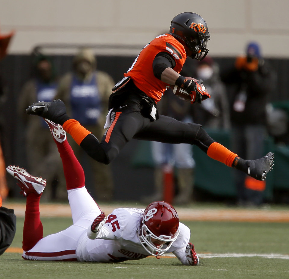 Oklahoma State's Josh Stewart (5) leaps over Oklahoma's Caleb Gastelum (45) during the Bedlam college football game between the Oklahoma State University Cowboys (OSU) and the University of Oklahoma Sooners (OU) at Boone Pickens Stadium in Stillwater, Okla., Saturday, Dec. 7, 2013. Photo by Bryan Terry, The Oklahoman