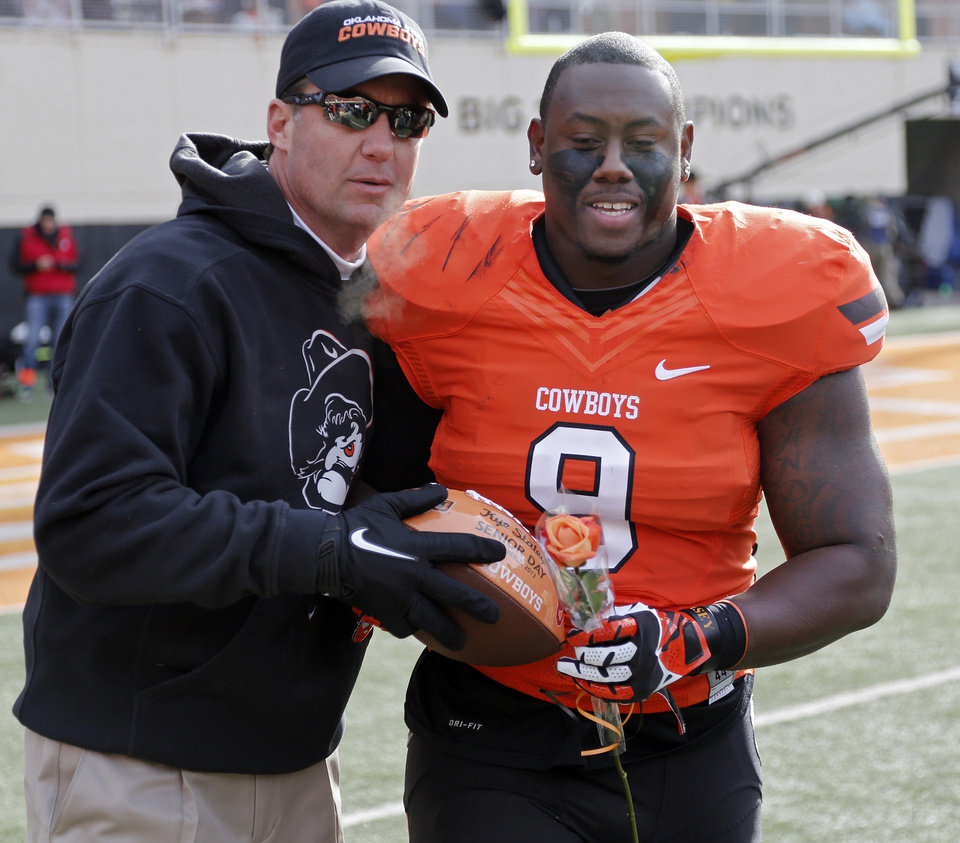 Photo - Coach Mike Gundy gives Oklahoma State's Kye Staley (9) a football on senior day during the Bedlam college football game between the Oklahoma State University Cowboys (OSU) and the University of Oklahoma Sooners (OU) at Boone Pickens Stadium in Stillwater, Okla., Saturday, Dec. 7, 2013. Photo by Chris Landsberger, The Oklahoman