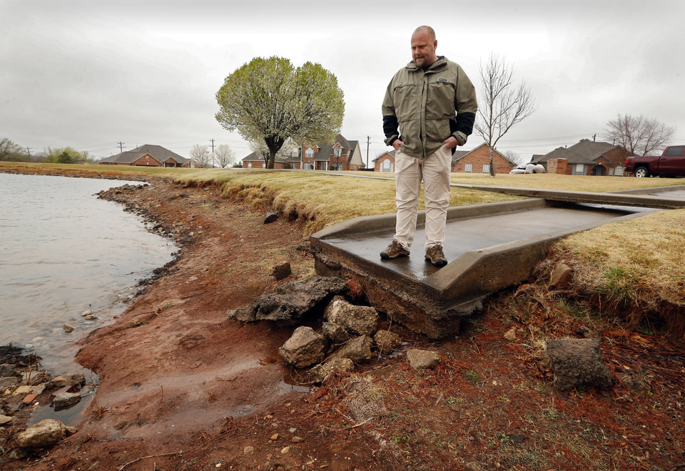 Photo -  Jeff Puckett, president of the Summit Lakes Homeowners Association, talks about problems with the community's dam, which is seeping and has been placed on the