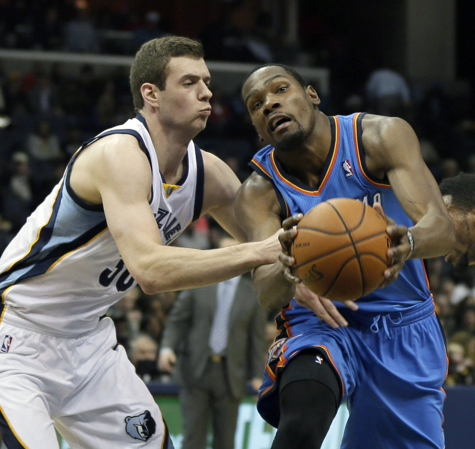 Photo - Oklahoma City Thunder's Kevin Durant, right, drives past Memphis Grizzlies' Jon Leuer in the first half of an NBA basketball game in Memphis, Tenn., Wednesday, Dec. 11, 2013. (AP Photo/Danny Johnston)