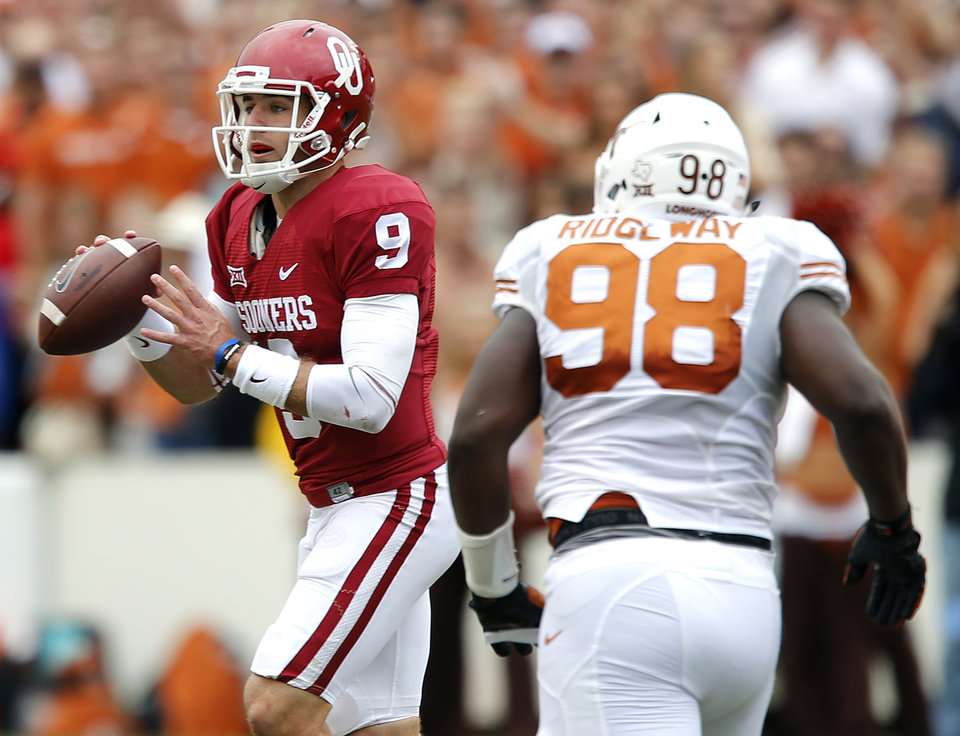Photo - Oklahoma's Trevor Knight (9) looks to pass the ball under the pressure of Texas' Hassan Ridgeway (98) during the college football game between the University of Oklahoma Sooners (OU) and the University of Texas Longhorns (UT) during the Red River Showdown at the Cotton bowl in Dallas, Texas on Saturday, Oct. 11, 2014. Photo by Chris Landsberger, The Oklahoman