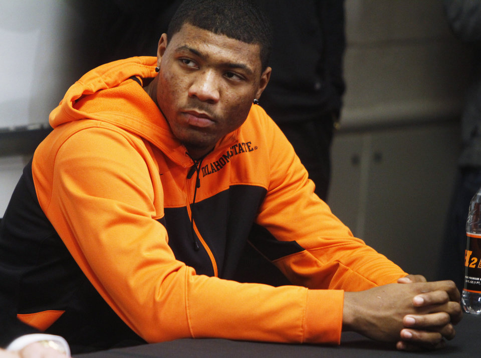 Photo - Oklahoma State basketball player Marcus Smart looks on as coach Travis Ford addresses media members at a press conference held in Gallagher Iba Arena on Sunday, Feb. 9, 2014, in regards to Smart shoving a fan in an altercation during a game Saturday, Feb. 8, 2014. Smart was given a three game suspension by the Big 12 conference and Oklahoma State. Photo by KT King/The Oklahoman