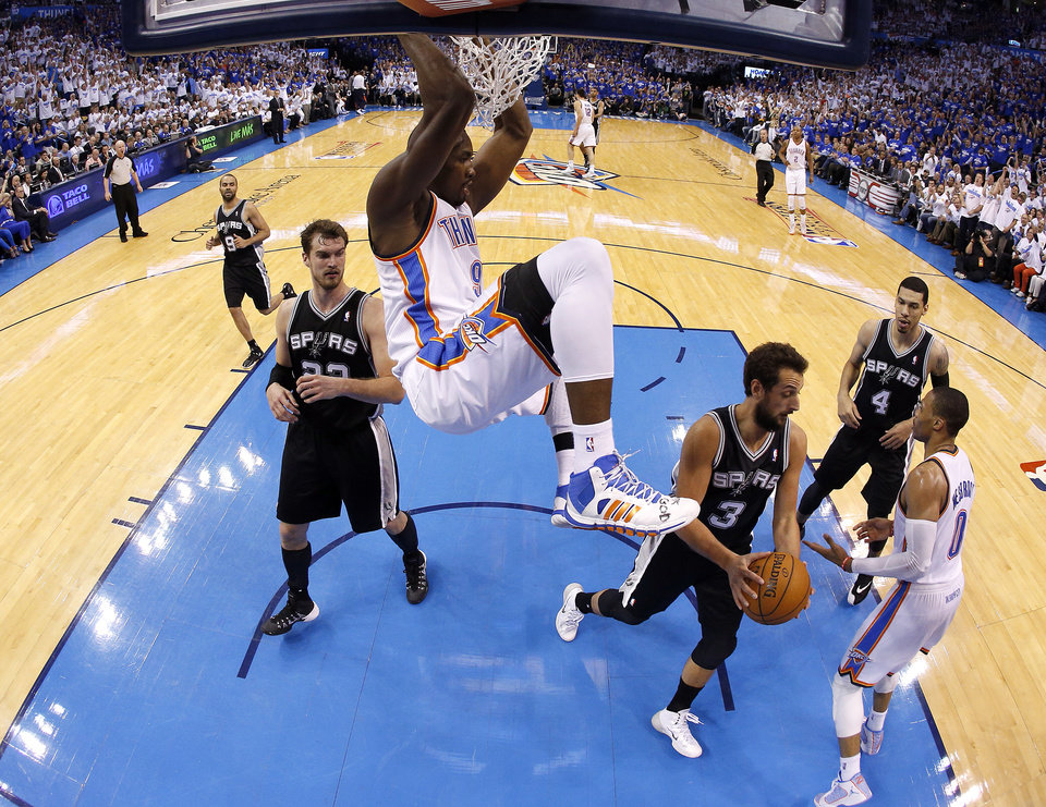Photo - Oklahoma City's Serge Ibaka (9) hangs on the rim after a dunk during Game 4 of the Western Conference Finals in the NBA playoffs between the Oklahoma City Thunder and the San Antonio Spurs at Chesapeake Energy Arena in Oklahoma City, Tuesday, May 27, 2014. Photo by Bryan Terry, The Oklahoman
