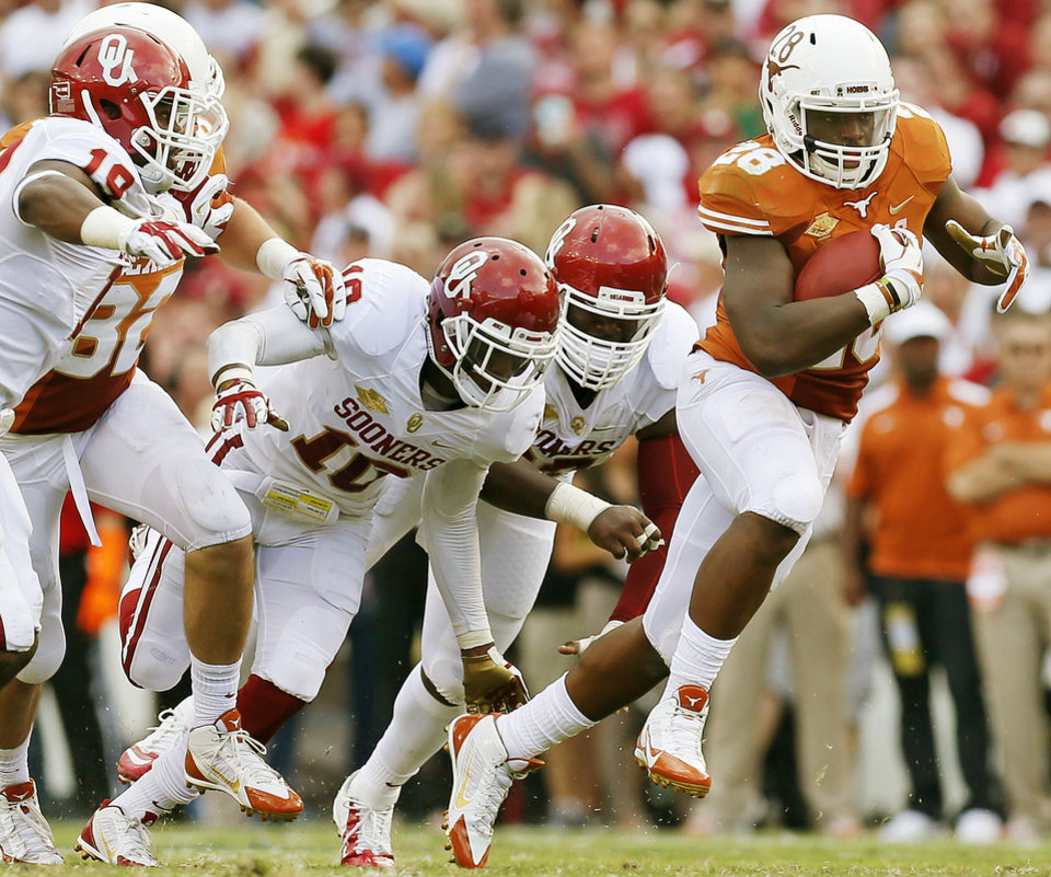 The OU defense chases UT's Malcolm Brown (28) on a carry in the second quarter during the Red River Rivalry college football game between the University of Oklahoma Sooners and the University of Texas Longhorns at the Cotton Bowl Stadium in Dallas, Saturday, Oct. 12, 2013. Photo by Nate Billings, The Oklahoman