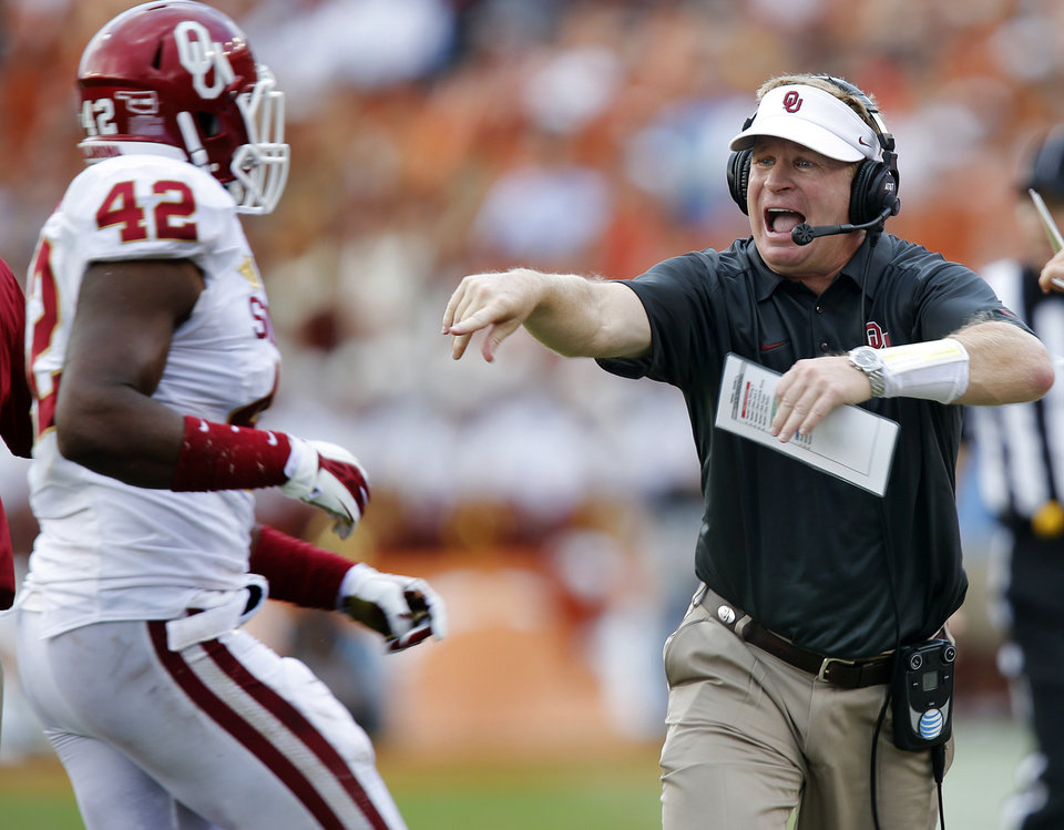 Photo - Mike Stoops yells at OU's Dominique Alexander (42) during the Red River Rivalry college football game between the University of Oklahoma Sooners (OU) and the University of Texas Longhorns (UT) at the Cotton Bowl Stadium in Dallas, Saturday, Oct. 12, 2013. Photo by Chris Landsberger, The Oklahoman