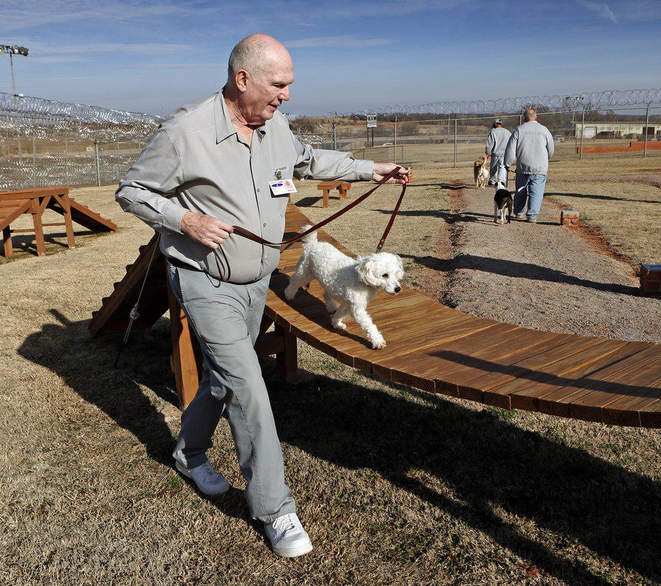 Photo - Above:  Inmate dog trainer Bill Miller works Jan. 29 with maltese/poodle mix, Jesse, at the Lexington Assessment and Reception Center in Lexington.  PhotoS by Steve Sisney, The Oklahoman  STEVE SISNEY -  THE OKLAHOMAN